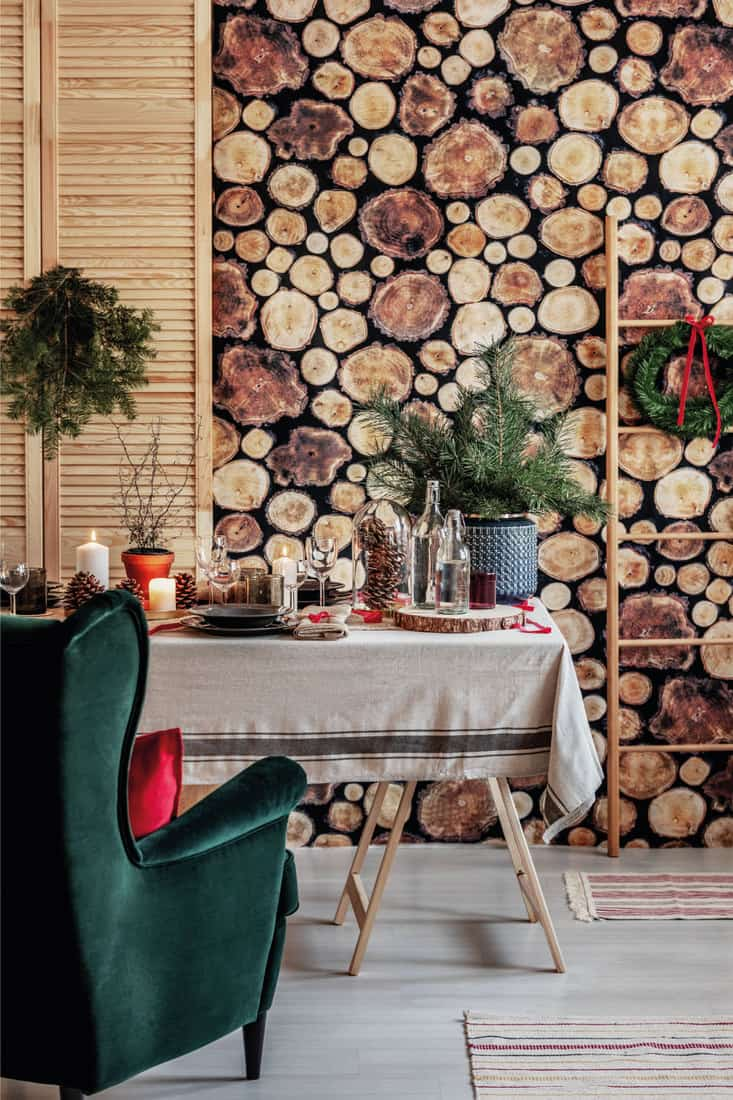 Log of wood wallpaper on the wall of stylish dining room set for Christmas