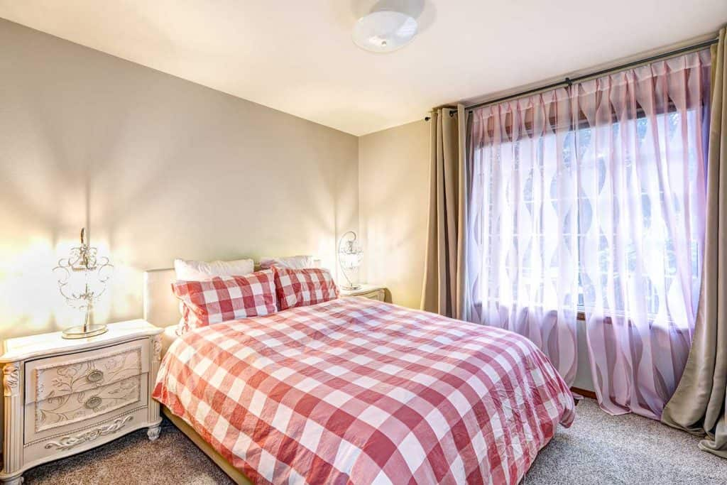Lovely bedroom interior with soft beige walls and checkered sheets