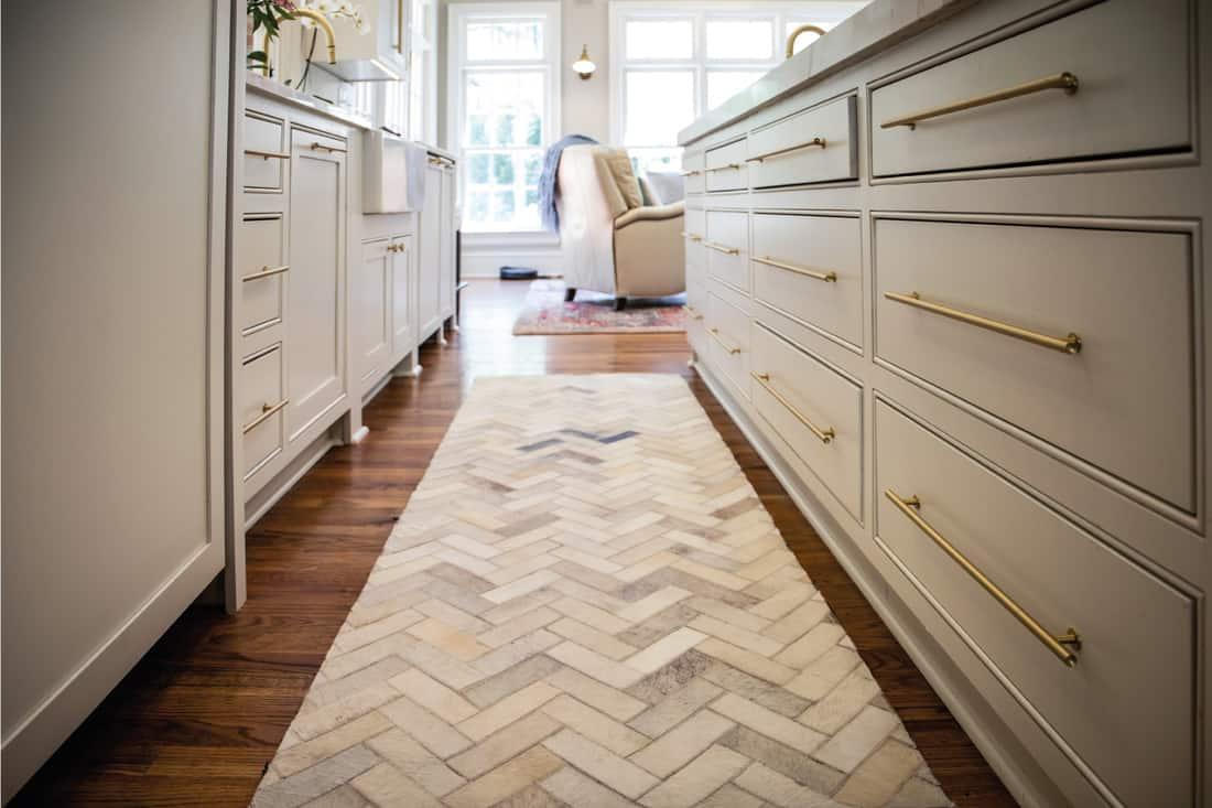 Lower view of a kitchen hardwood floor with herringbone rug