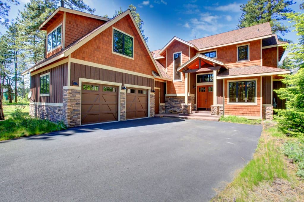 Luxurious exterior of a two storey farmhouse with vinyl sidings, weathered shingles, and a huge driveway