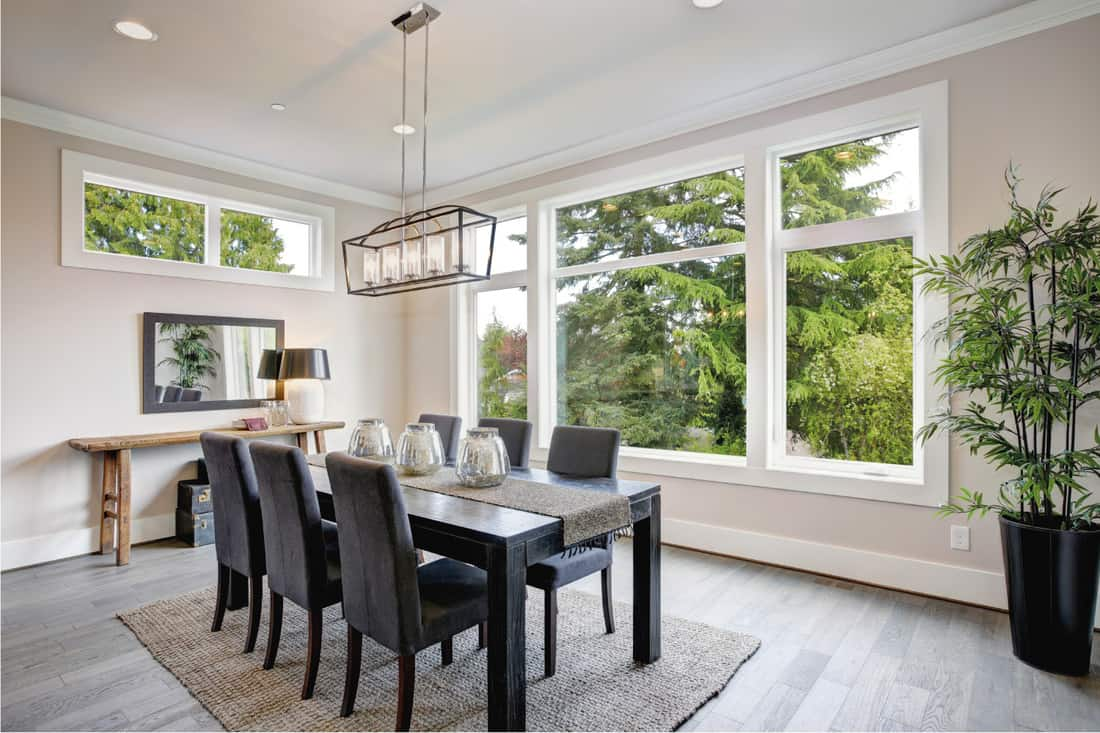Luxurious modern dining room boasts a black dining table illuminated by a rectangular chandelier and a large wall of windows