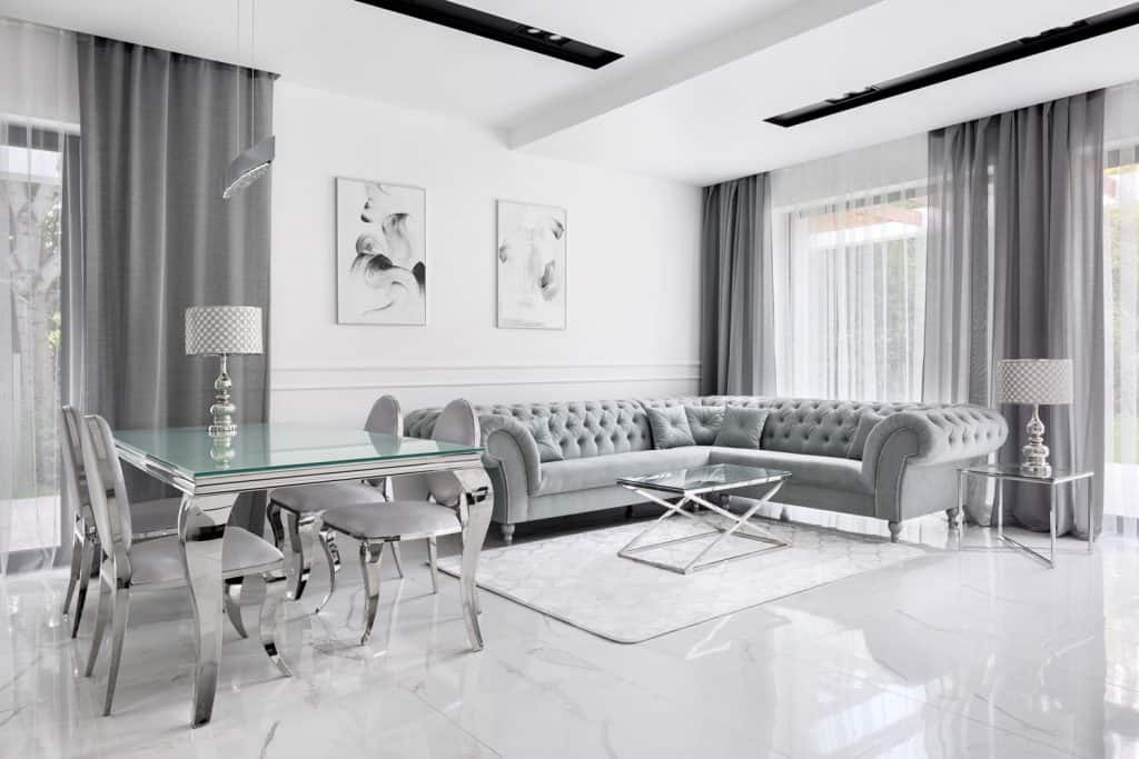 Luxurious modern living room with gray colored curtains, gray sectional sofas, gray dining tables and chairs