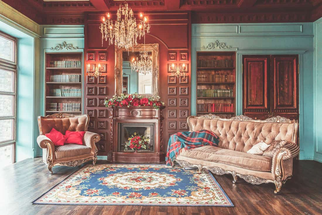 Luxury classic interior of home library. Sitting room with bookshelf, books, arm chair, sofa and fireplace