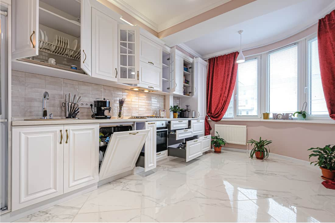 Luxury modern white kitchen interior with open doors and drawers