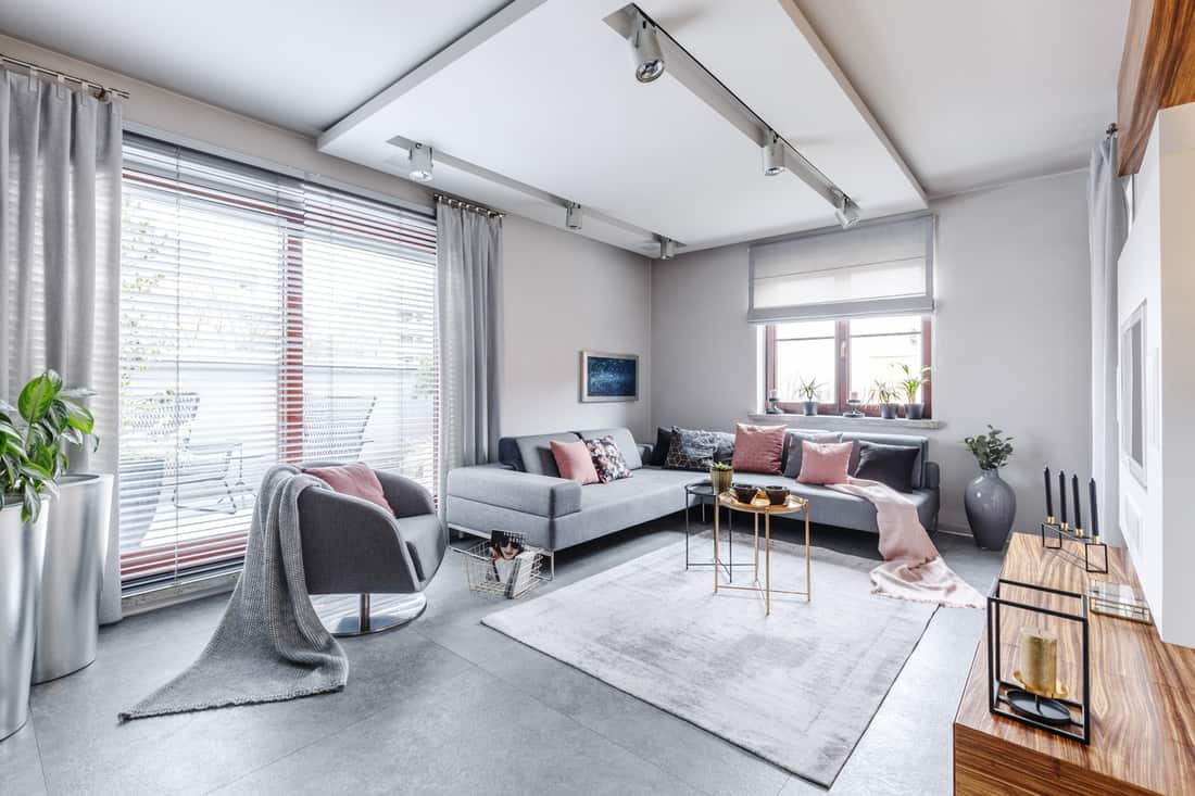 Modern interior with large gray corner sofa and armchair decorated with pillows and blankets in a bright cosy living movie room with light from big glass door to balcony, wooden elements and decorations