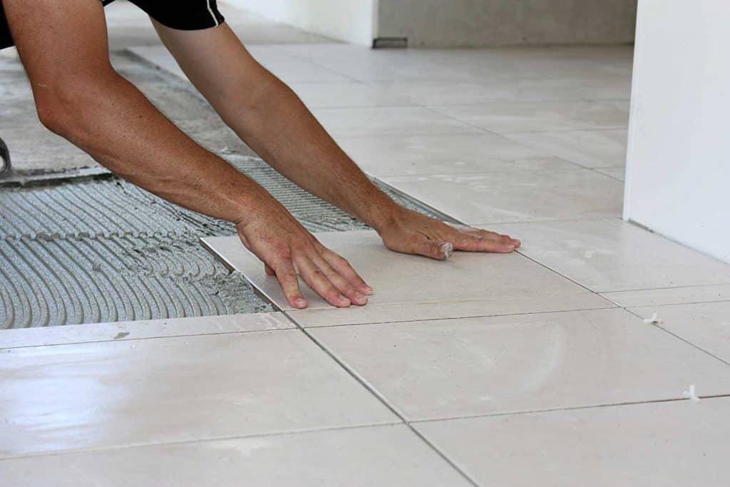 Man laying tile on floor