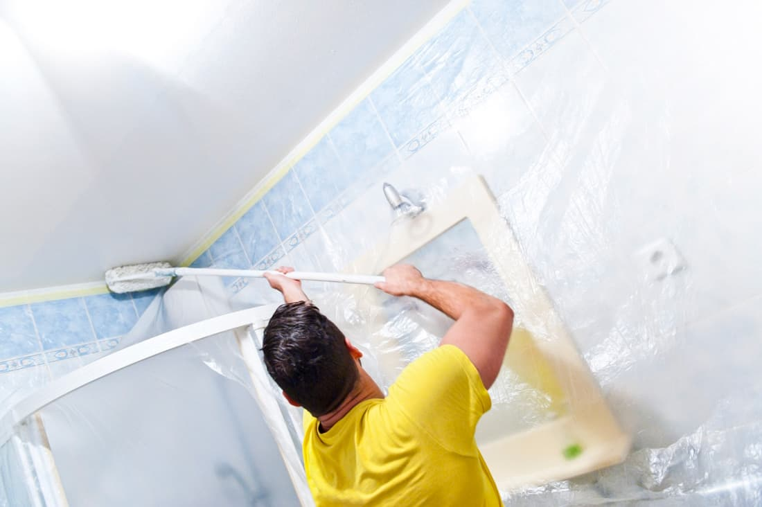 Man painting the inside of a house bathroom