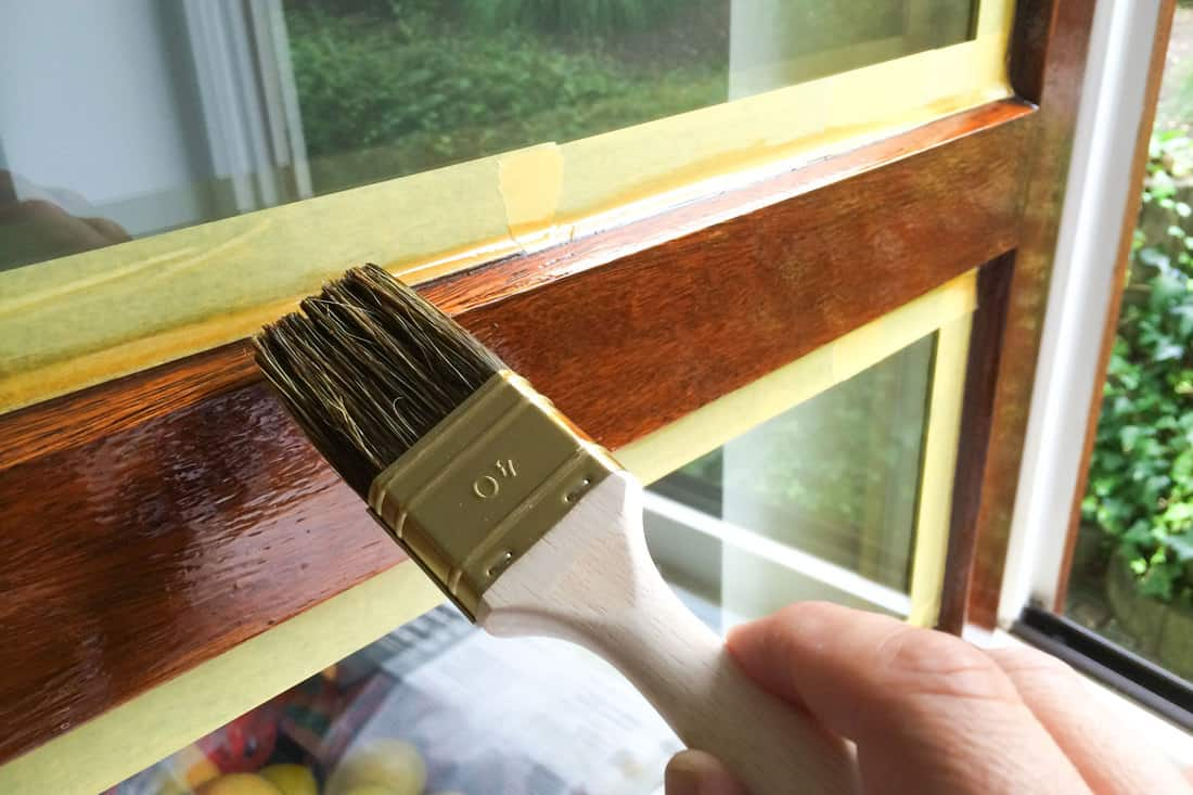 Man repaint a window frame with brown varnish