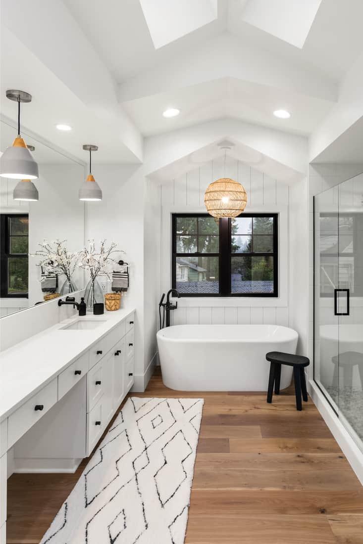 Master bathroom with double vanity with engineered wood flooring