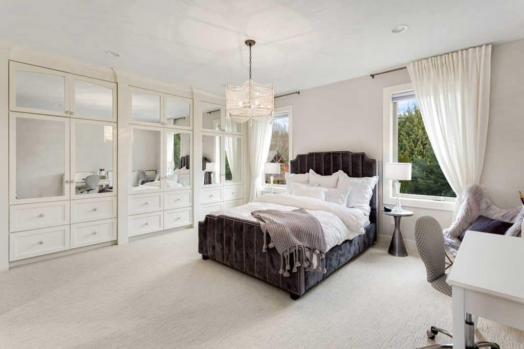 Master bedroom in new luxury home with large windows, chandelier, carpet, and elegant decor