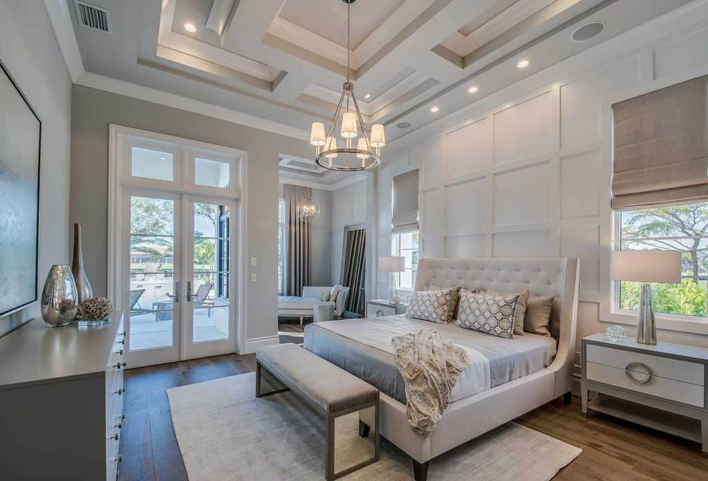 Master bedroom with high coffered ceiling and wainscoting wall, walk out french glass doors to the back patio and pool area