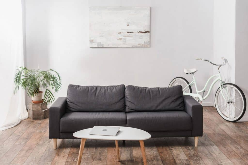 Minimalist themed small living room with a dark gray sofa, white coffee table, and wooden weathered flooring