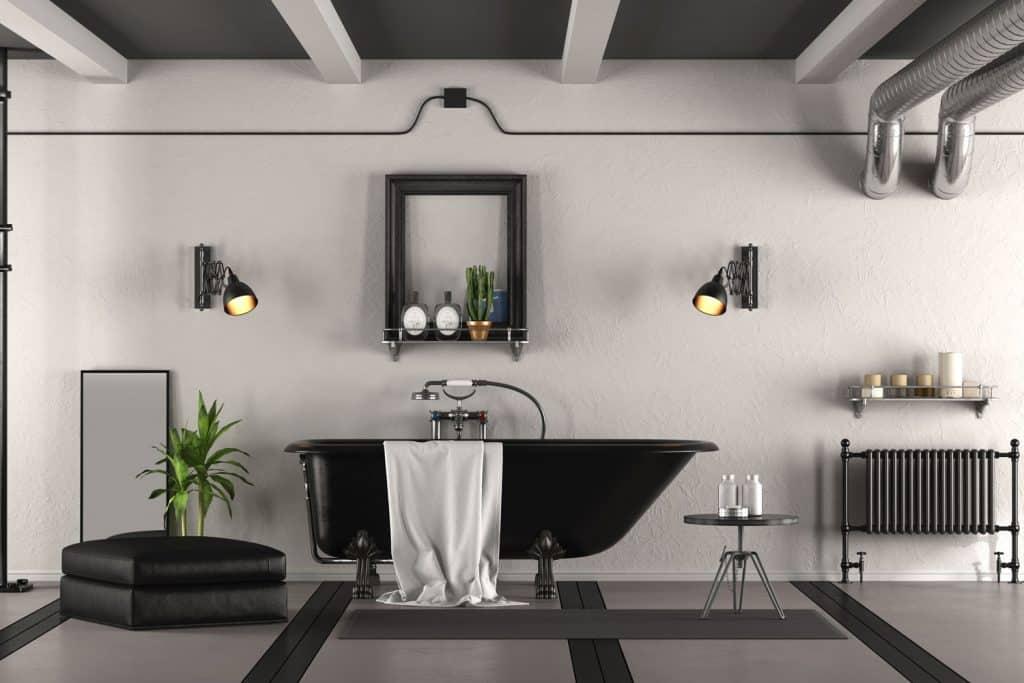 Minimalist inspired bathroom with a black bathtub and gray tiled flooring