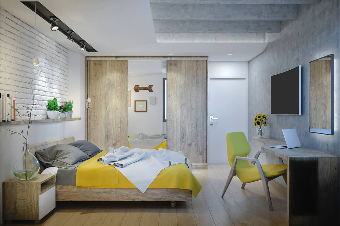 Modern and elegant bedroom with wooden panels and yellow details
