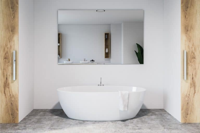 Modern bathroom interior with white walls, concrete floor, and white bathtub with large mirror hanging above it, How To Hang A Heavy Mirror [3 Ways]