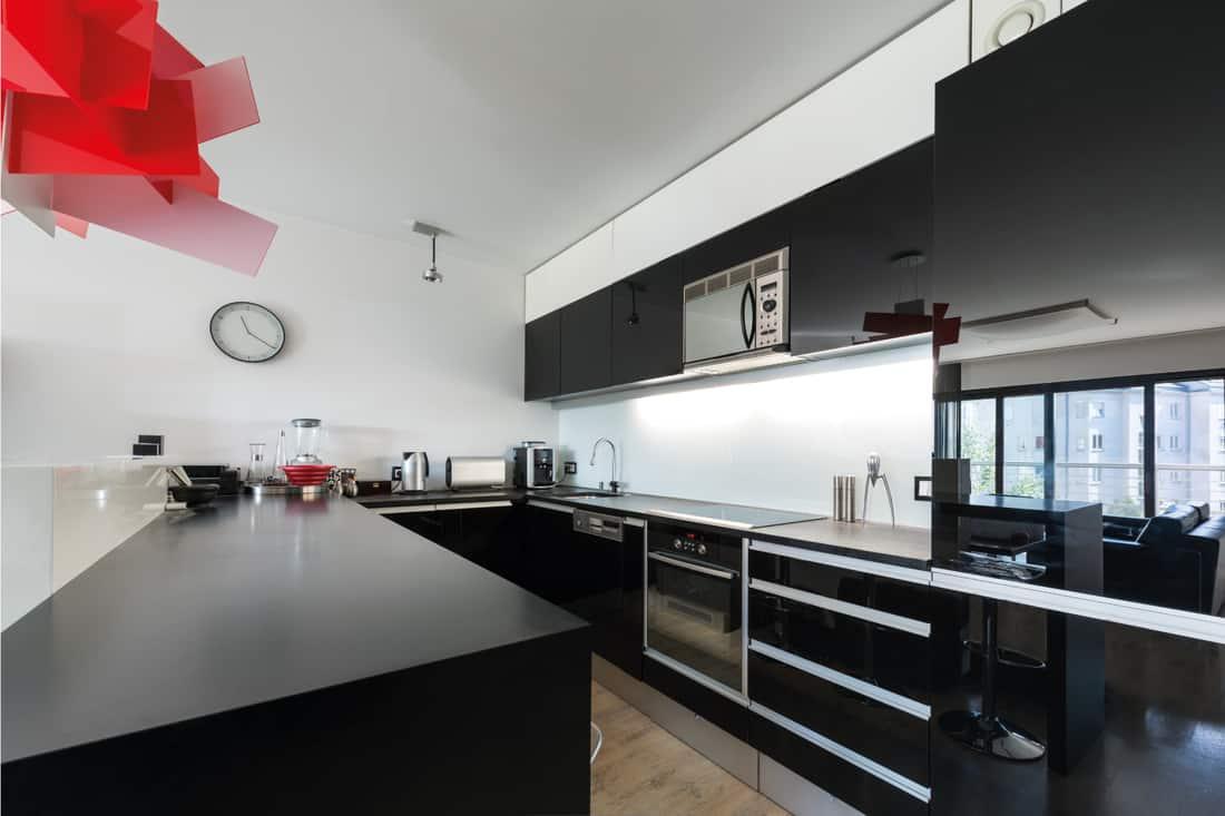 Modern black and white kitchen interior with sleek mirrored cabinets