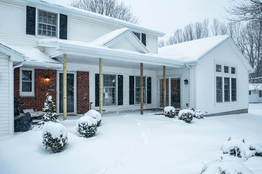 Modern contemporary home with wooden paneled sidings covered in snow due to snow blizzard