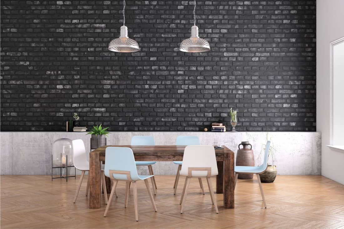 Modern dining room interior with wooden table, minimalist chairs and black accent brick wall