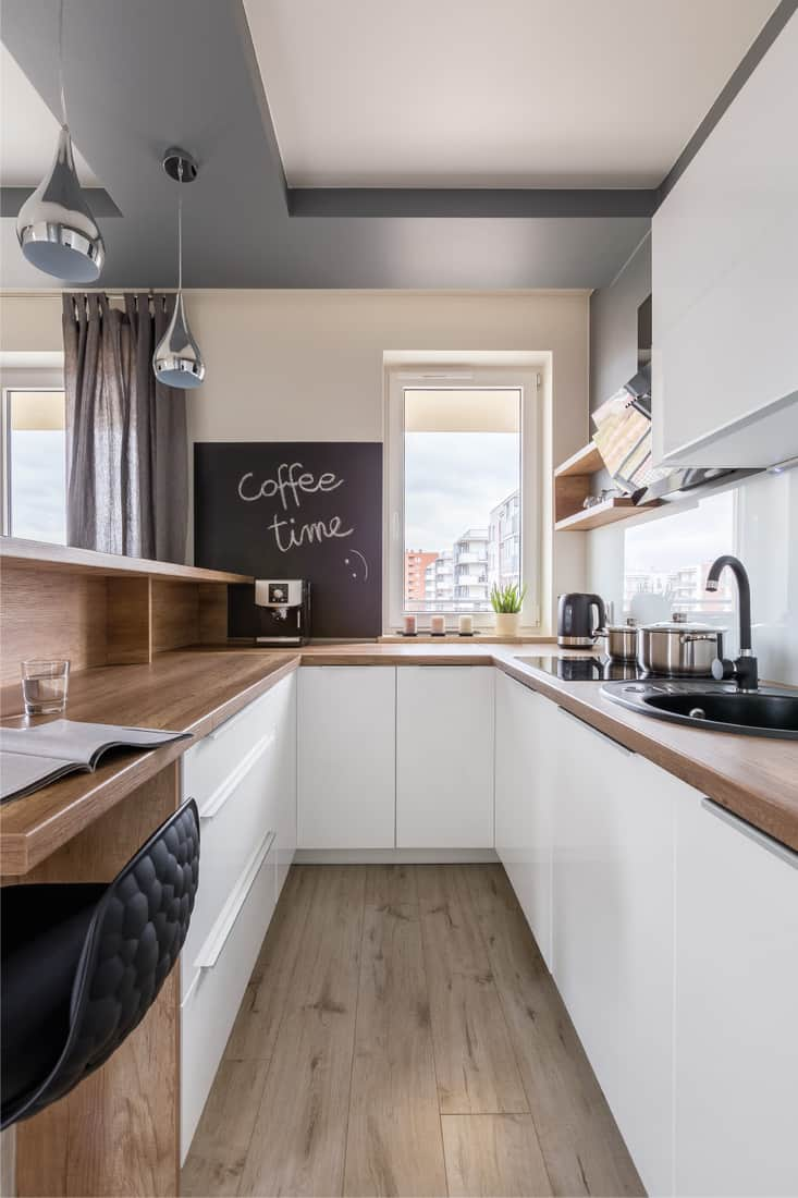 Modern kitchen with wooden counter, white unit and blackboard
