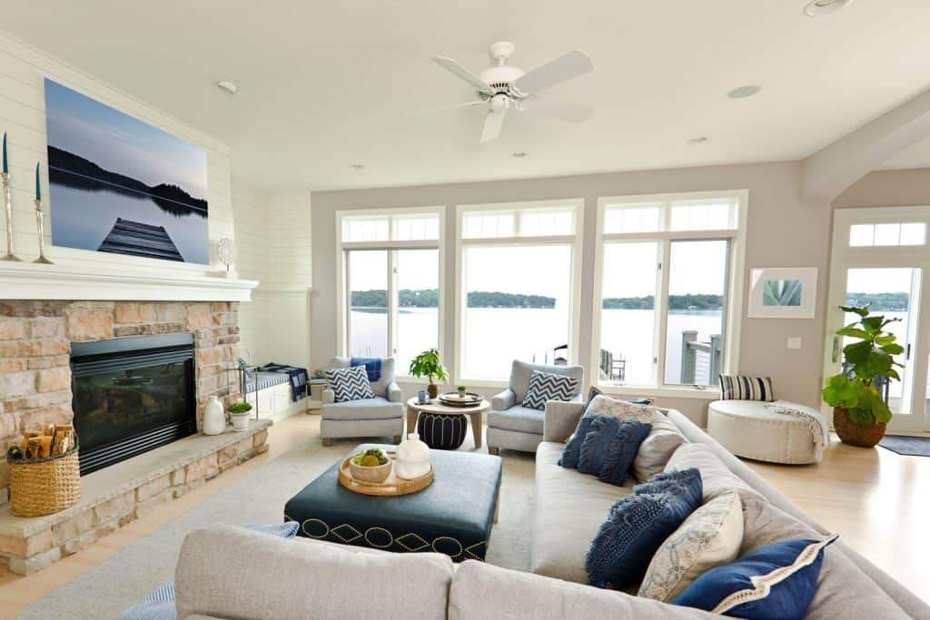Modern living room with white painted walls, light gray sectional sofas with blue and white throw pillows, and a huge picture window on the background