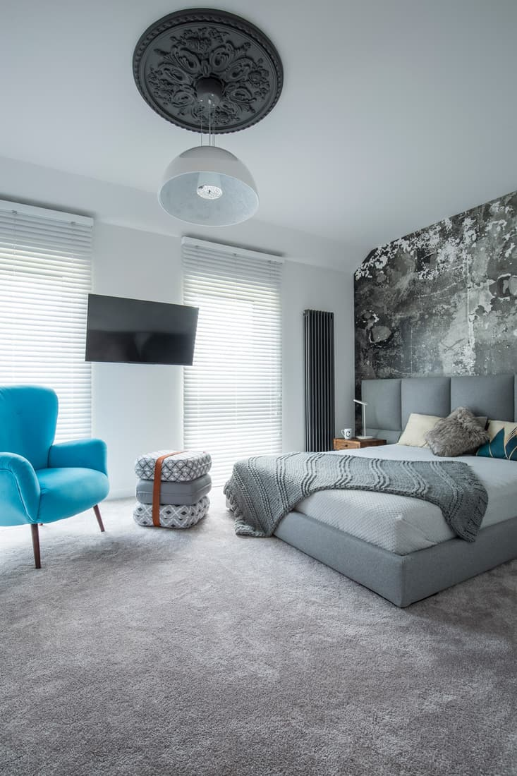 Modern luxury bedroom with gray carpet and monochromatic walls