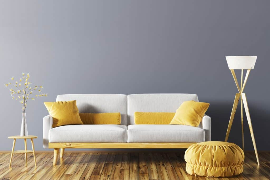 Modern minimalist themed living room with a hardwood flooring, white wooden framed sofa, yellow ottoman, and a small indoor plant on the side