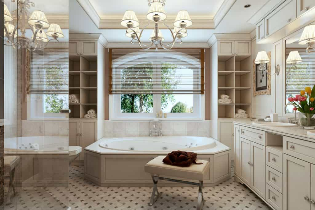 Modern Victorian themed bathroom with white painted cabinetry, octagon shaped bathtub and a small window