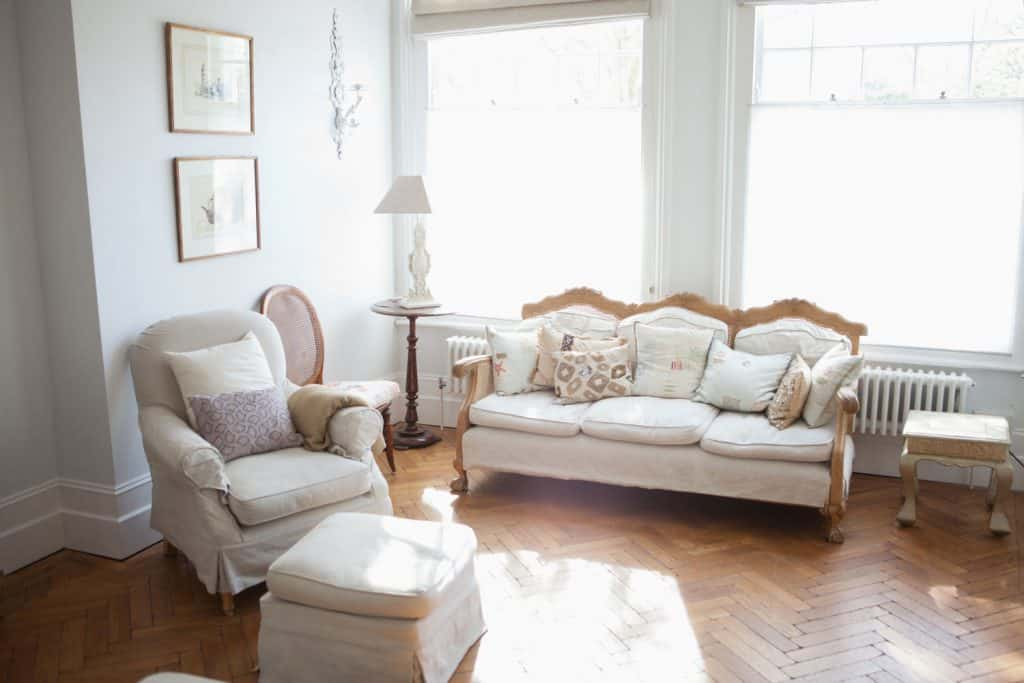 Modern Victorian themed living room with white sofas, comfortable white accent chair with a white ottoman infront