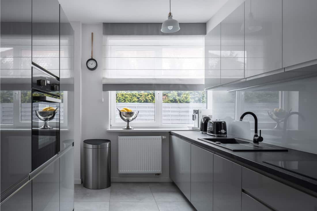 Narrow kitchen with window and modern roman shade, gray furniture