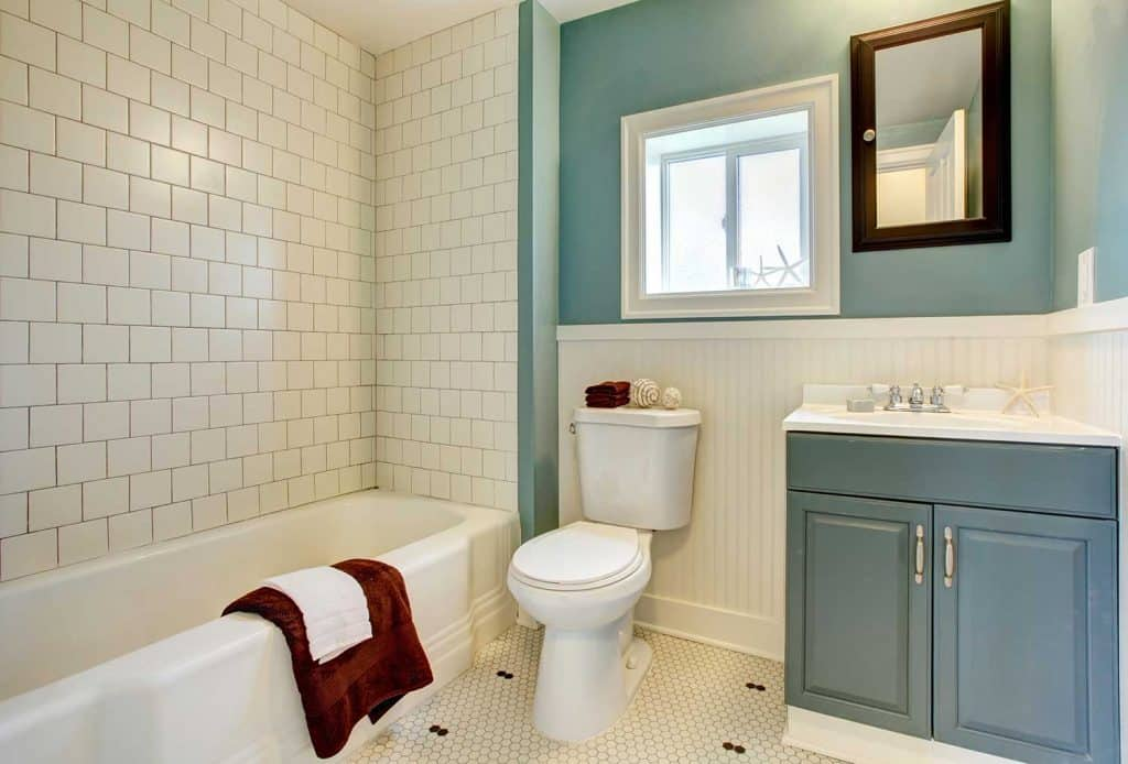 New remodeled blue bathroom with classic white tile