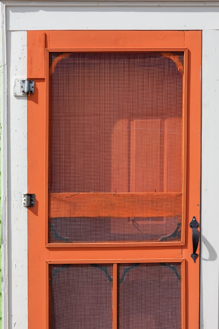Old-fashioned wooden screen door painted bright orange