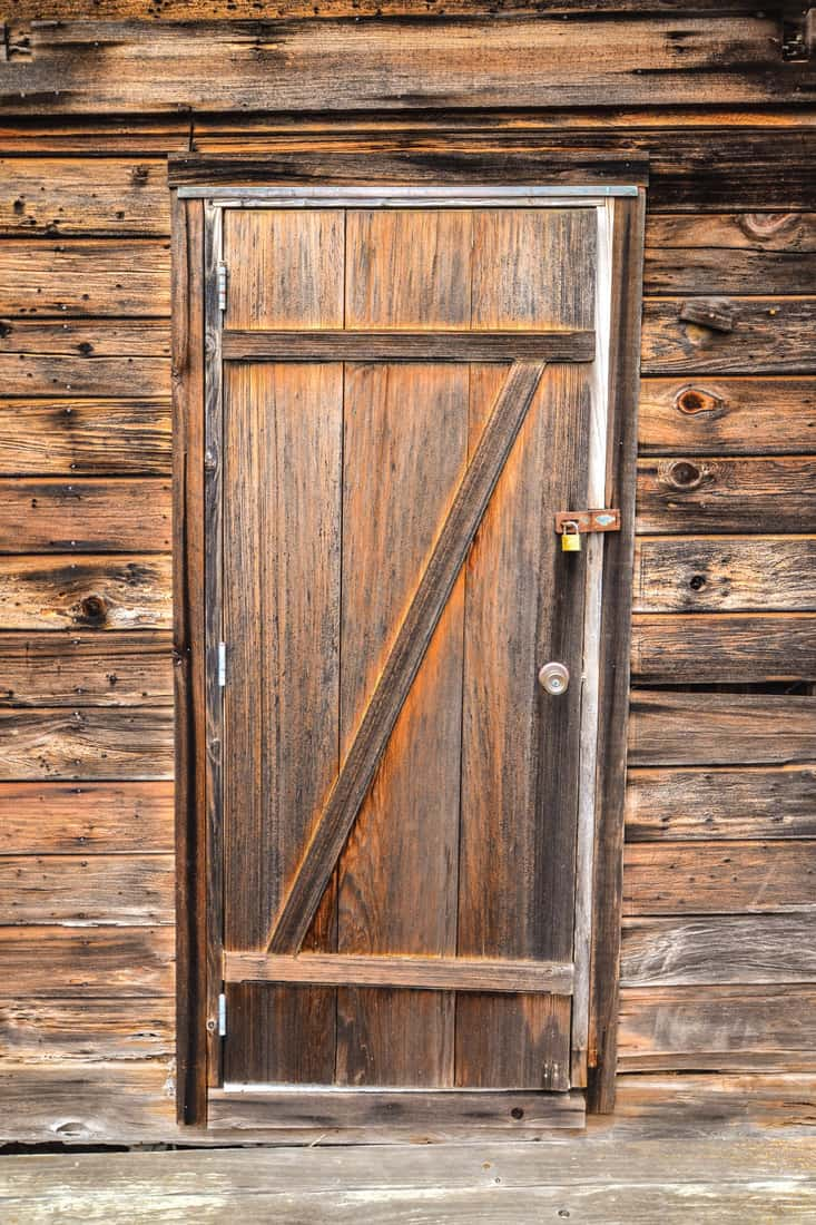 Old wood door with lock and redwood siding