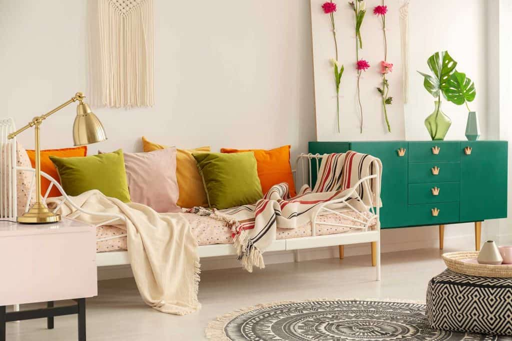 Olive green, pastel pink, yellow and orange pillows on single metal bed with patterned bedding in boho bedroom interior for girl
