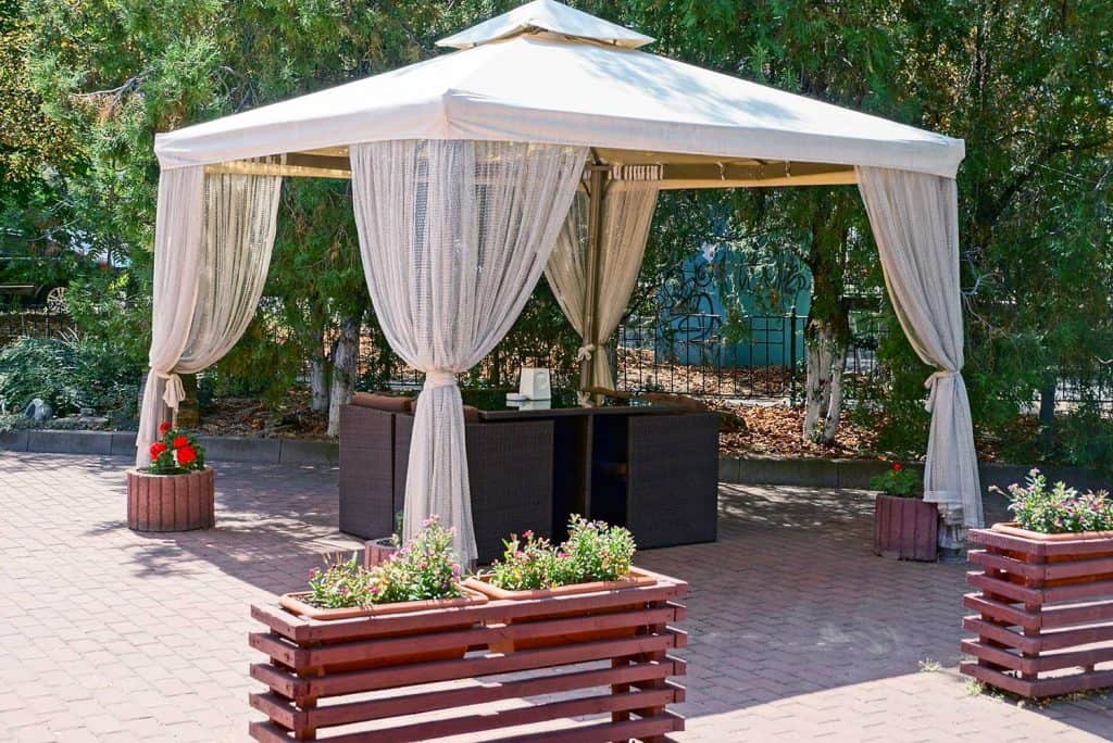 Outdoor gazebo with curtains and furniture on the sidewalk in the park