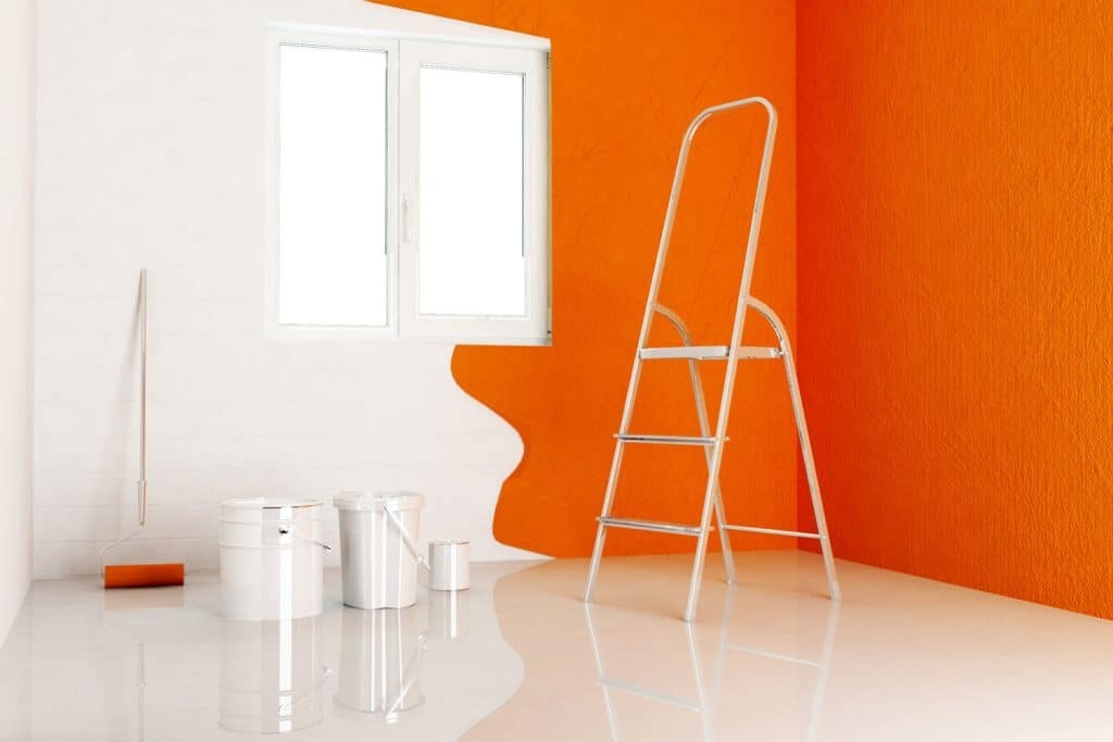 Painting materials placed on the flooring of a spacious orange colored living room
