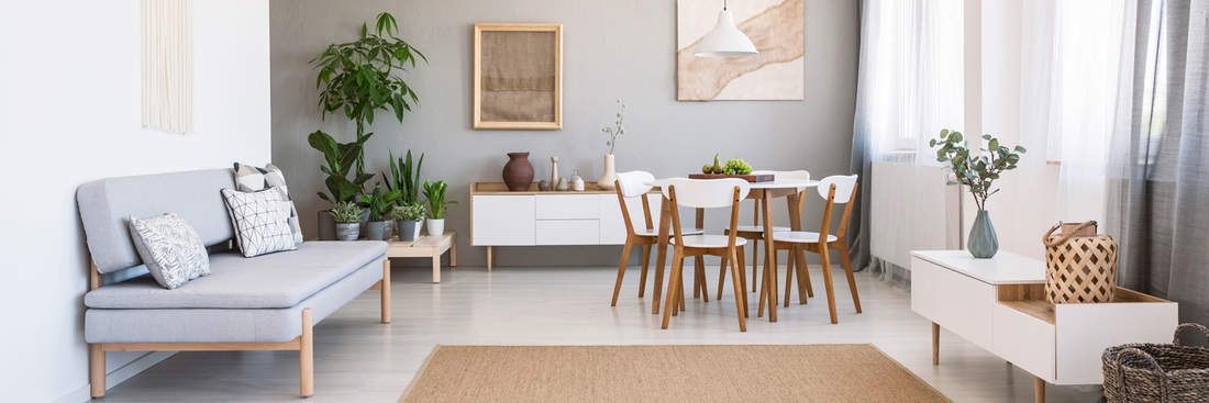 Panorama of a bright, spacious living and dining room interior with white, wooden furniture, gray sofa and plants