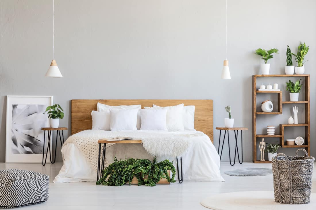 Patterned pouf and basket in bright bedroom interior with lamps, plants and poster next to bed