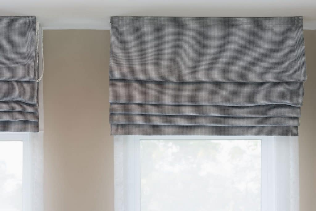 Perfectly folded gray curtains on a window