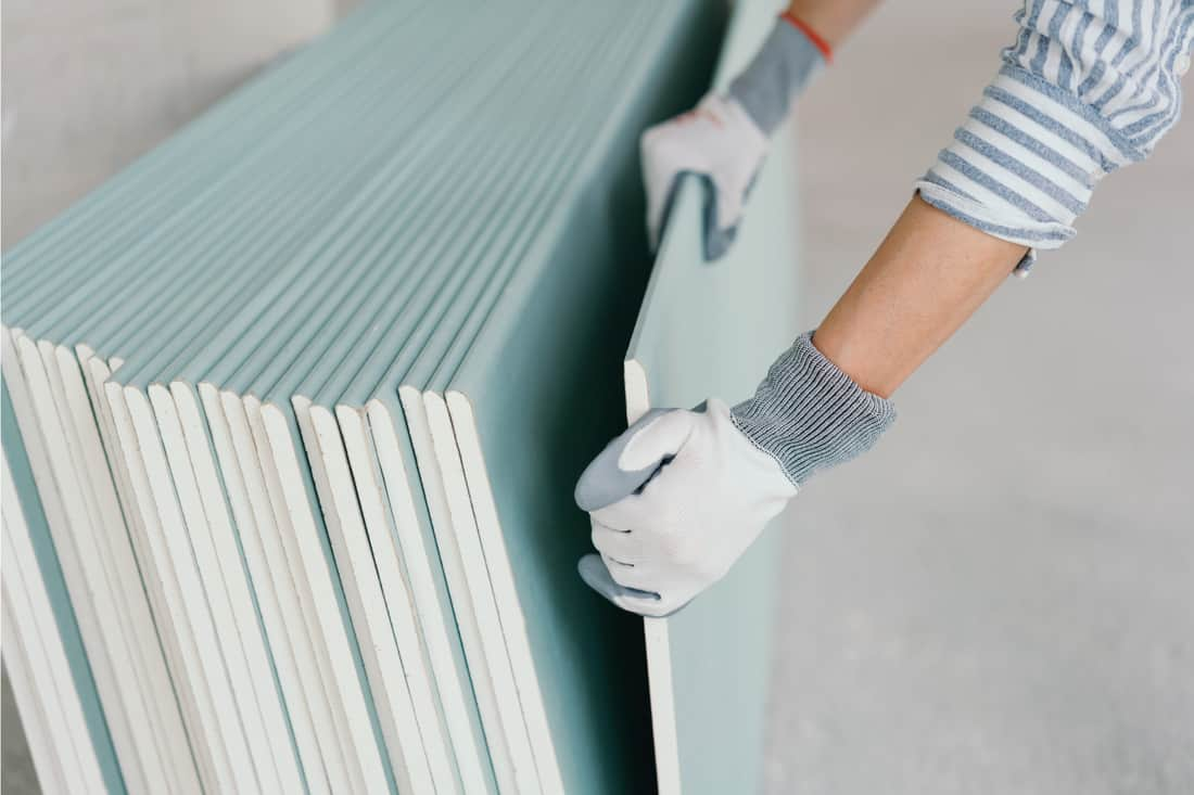 Person wearing protective gloves grabbing a sheet of chip board for use in interior building construction