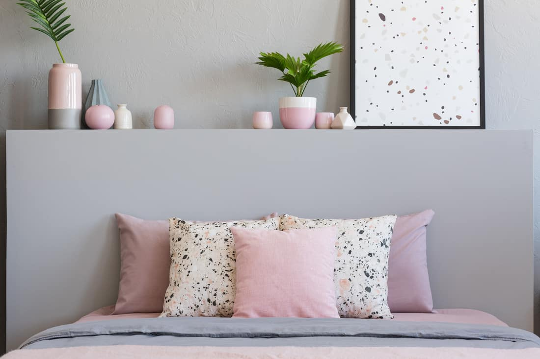 Pink and patterned pillows on bed with headboard in grey bedroom interior