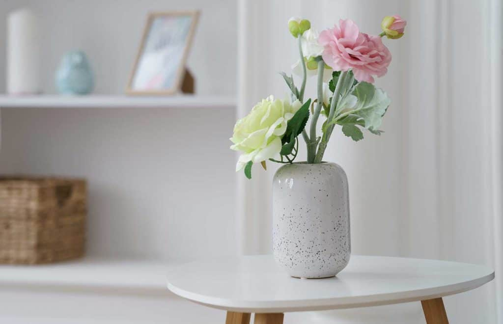 Pink and yellow roses in modern white vase on white table