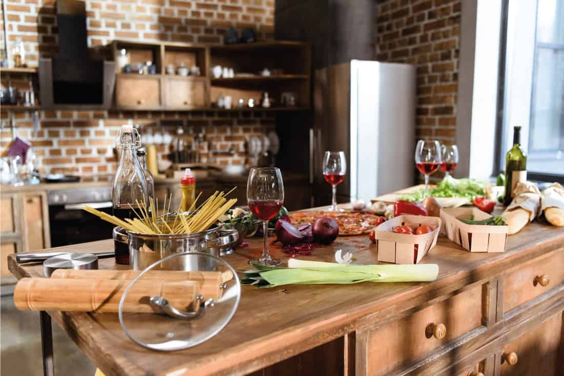 Pizza, wine and vegetables ready for party on a wooden island table