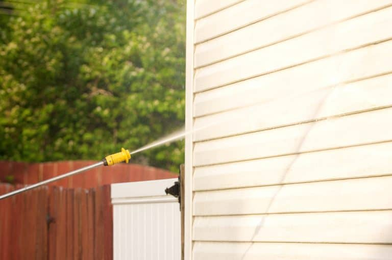 Pressure washing a dirty house vinyl siding