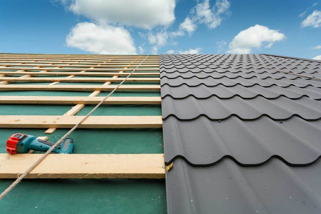 Roof with metal tile, screwdriver and roofing iron