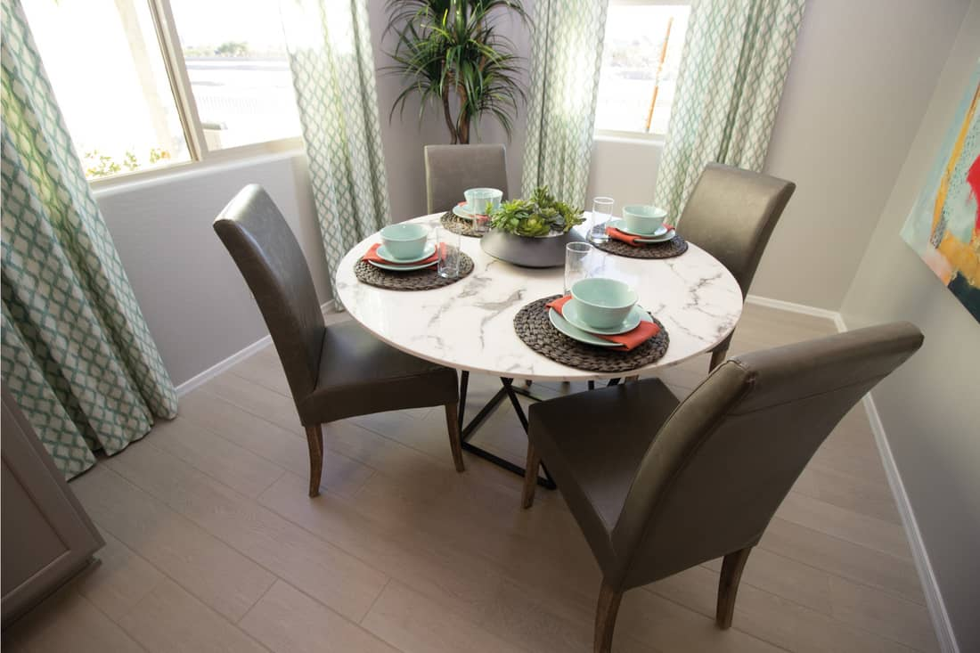 Round marble table with high back chairs and place settings