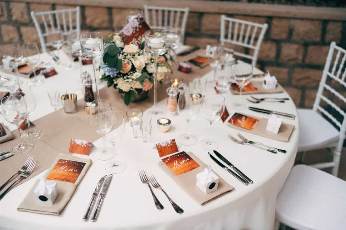 Round table with white tablecloth with brown runner on table