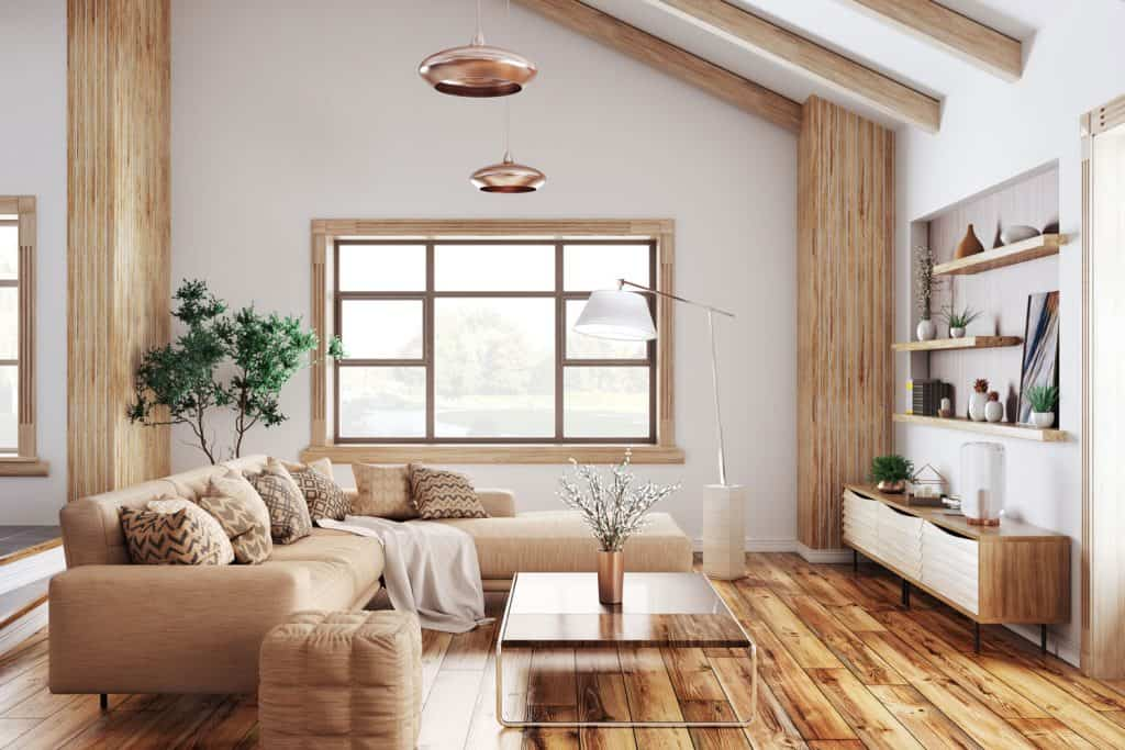 Rustic farmhouse themed living room with wooden flooring, cream colored sectional sofa and wooden coffee table infront, and a small beige ottoman