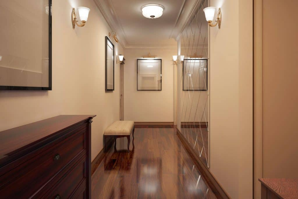 Rustic hallway with hardwood flooring, cream colored walls, with a wooden console table on the side