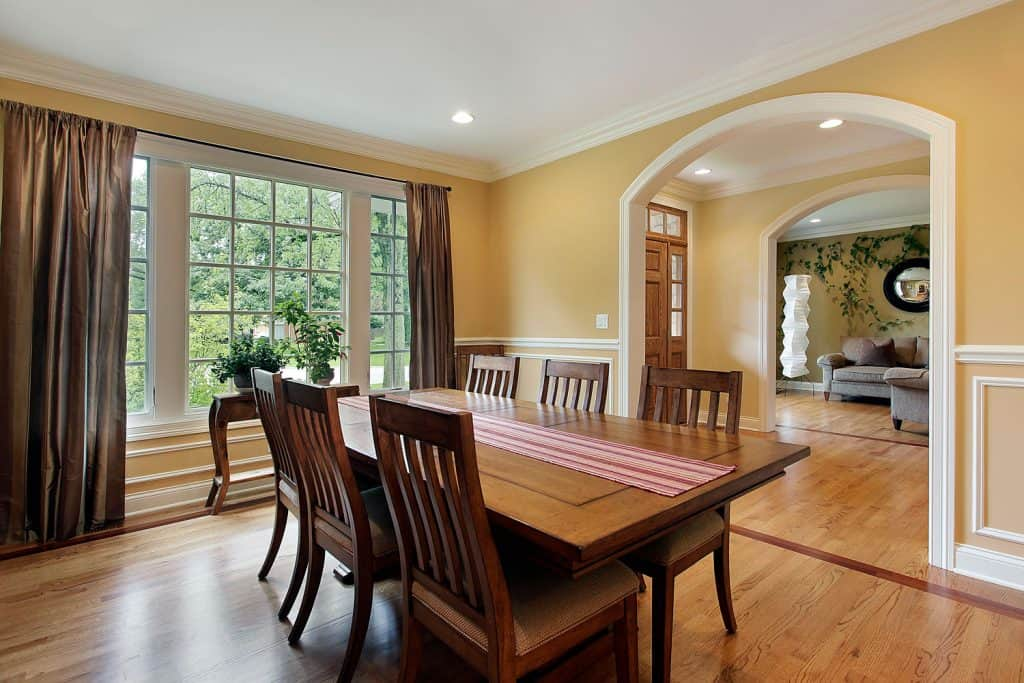 Rustic kitchen with light yellow colored walls, wooden dining tables and chairs matched with wooden flooring