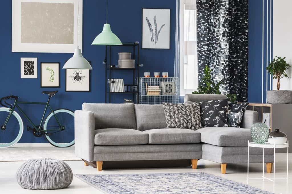 Scandinavian themed living room with blue painted wall, mock up picture frames, a small gray sectional sofa with a gray round ottoman on the side